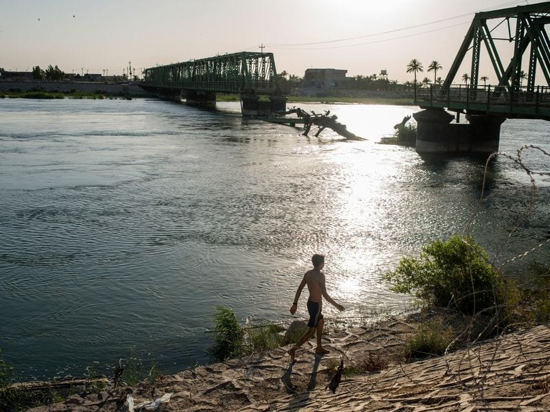 An Iraqi boy walking by the Euphrates during sunset. Photograph by Alex Kay Potter